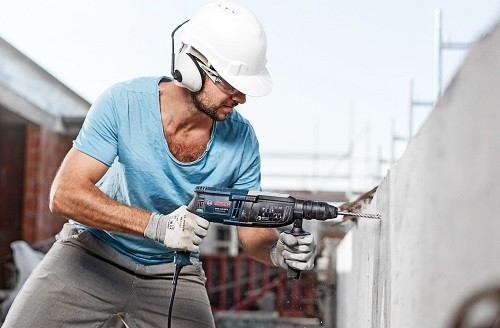 Man Drilling Wall With Hammer Drill